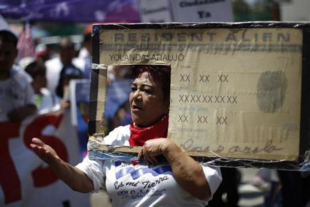 Rosa Ayala carries a Resident Alien placard during the International Workers Day and Immigration Reform March on May Day in Los Angeles, California May 1, 2013. REUTERS/David McNew