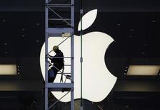 Trabalhador é visto em frente ao símbolo da Apple em Hong Kong, na China. A Apple rebateu às acusações do Departamento de Justiça dos Estados Unidos de que conspirou com editoras para elevar os preços de livros eletrônicos, dizendo que negociou com uma série de editoras separadamente e fez diferentes acordos com cada uma. 10/04/2013 REUTERS/Bobby Yip