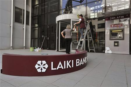 Workmen dismantle a sign of the Cyprus Popular Bank at its headquarters in the Cypriot capital Nicosia, May 15, 2013. REUTERS/Yiannis Nisiotis