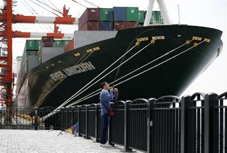 A man fishes near a cargo ship at a port in Tokyo April 18, 2013. REUTERS/Issei Kato