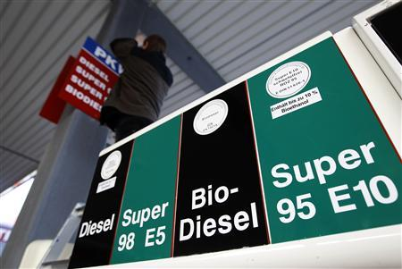 A petrol station employee fixes a sign including the new ethanol E10 fuel at a highway service station in Soltau between Hamburg and Hanover March 1, 2011. REUTERS/Christian Charisius