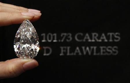 A Christie's member of staff displays a pear-shaped, D colour, flawless diamond of 101.73 carats during an auction preview in Geneva April 30, 2013. REUTERS/Denis Balibouse