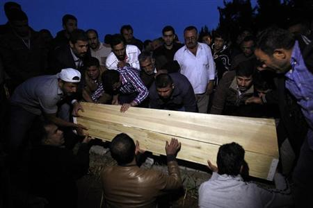 Relatives of 39-year-old Mehmet Tas, a victim of a car bomb attack, lower his coffin into a grave in the town of Reyhanli in Hatay province near the Turkish-Syrian border May 15, 2013. REUTERS/Umit Bektas