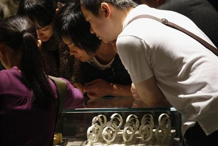 Customers lean over an empty display case that was used to display gold bracelets at a jewellery store in Hong Kong April 26, 2013. REUTERS/Bobby Yip/Files