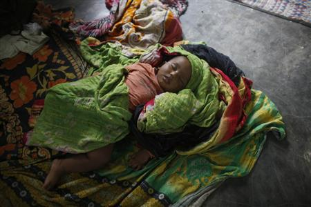 A child sleeps inside a shelter house before cyclone Mahasen approaches in Chittagong May 16, 2013. REUTERS-Andrew Biraj
