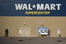Мужчина на скейте стоит около магазина Wal-Mart в Уиллистоне (Северная Дакота), 13 марта 2013 года. Квартальная прибыль Wal-Mart Stores Inc выросла, несмотря на падение продаж в американских магазинах, открытых как минимум год назад. REUTERS/Shannon Stapleton