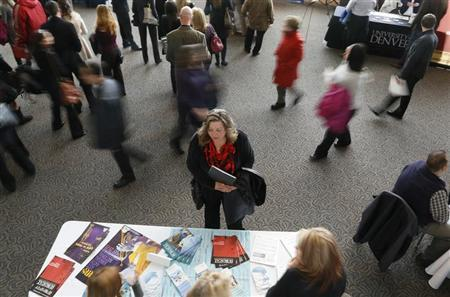 A job seeker (C) talks to an exhibitor at the Colorado Hospital Association health care career fair in Denver April 9, 2013. REUTERS/Rick Wilking