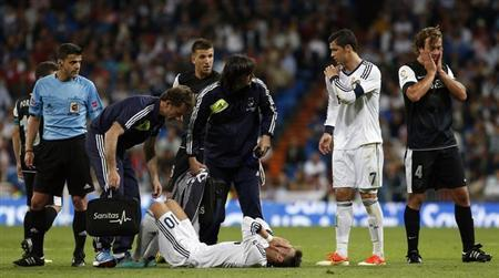 Real Madrid's Mesut Ozil lies on the pitch waiting for a stretcher during their Spanish first division soccer match against Malaga at Santiago Bernabeu stadium in Madrid May 8, 2013. REUTERS/Susana Vera