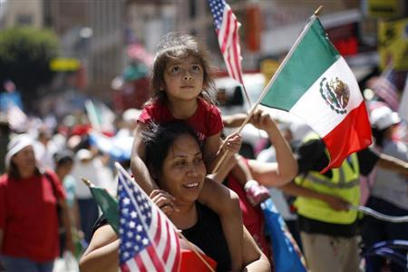 A child looks up as she rides among Mexican and American flags during the International Workers Day and Immigration Reform March on May Day in Los Angeles, California May 1, 2013. REUTERS/David McNew
