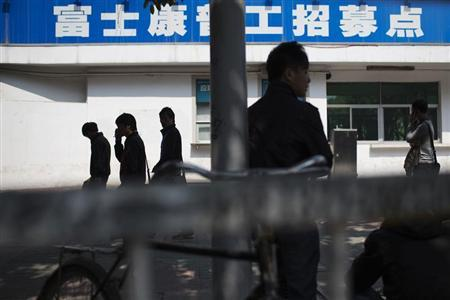 People walk past a closed job centre of Foxconn factory in the township of Longhua in Shenzhen, Guangdong province February 21, 2013. REUTERS/Tyrone Siu