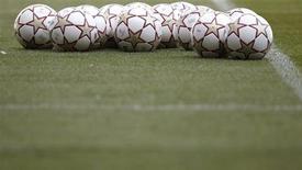 Футбольные мячи лежат на поле в Мадриде, 21 мая 2010 года. Матчи чемпионатов России, Украины, Испании, Англии, Германии, Италии, Франции и финал Кубка Испании пройдут в пятницу и выходные. REUTERS/Kai Pfaffenbach