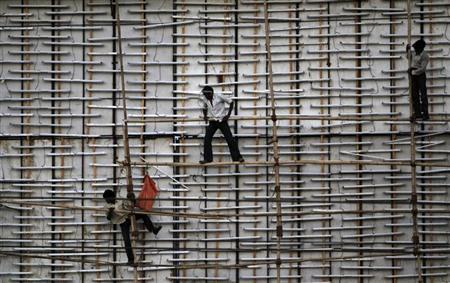 Workers install bamboo poles on a billboard under construction along a road on the outskirts of Ahmedabad May 11, 2013. REUTERS/Amit Dave