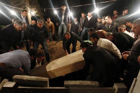 Relatives of 55-year-old Kemal Baz, a victim of a car bomb attack, lower his coffin into a grave in the town of Reyhanli in Hatay province near the Turkish-Syrian border May 15, 2013. REUTERS/Umit Bektas