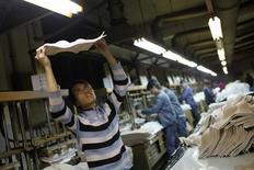 Salariés chinois dans une usine à Shanghai. La hausse des salaires dans les grandes agglomérations chinoises a ralenti en 2012, comme la croissance globale de l'économie, montrent vendredi les chiffres publiés par le Bureau national des statistiques. /Photo prise le 26 février 2013/REUTERS/Aly Song