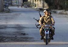 مقاتلون من الجيش السوري الحر على متن دراجة نارية في دير الزور يوم الخميس - رويترز