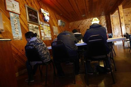 A group of illegal immigrants, who handed themselves in to U.S. Border Patrol, sit in a restaurant in Encino, Texas March 29, 2013. REUTERS/Eric Thayer