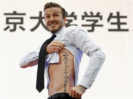 Former England captain David Beckham shows his tattoo after he was asked to by students at Peking University during his visit in Beijing in this March 24, 2013 file photo. REUTERS/Stringer/Files