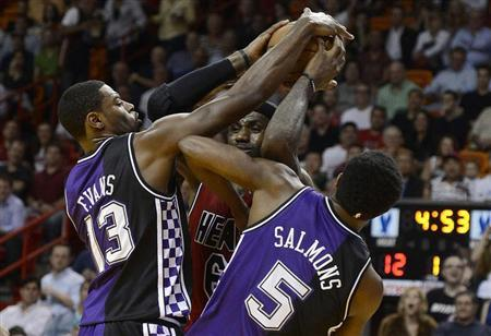 Miami Heat's LeBron James (C) is defended by Sacramento Kings' Tyreke Evans and John Salmons (R) during the first half of their NBA basketball game in Miami, Florida, February 26, 2013. REUTERS/Rhona Wise