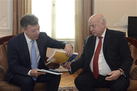 Colombia's President Juan Manuel Santos (L) receives a document from Jose Miguel Insulza, General Secretary of the Organization for the American States (OAS), during a meeting at presidential palace in Bogota May 17, 2013. REUTERS/Andres Piscov/Presidency/Handout