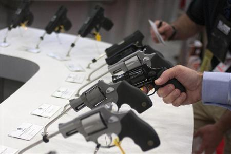 A man holds a gun in the exhibit hall of the George R. Brown Convention Center, the site for the National Rifle Association's (NRA) annual meeting in Houston, Texas May 3, 2013. . REUTERS/Adrees Latif