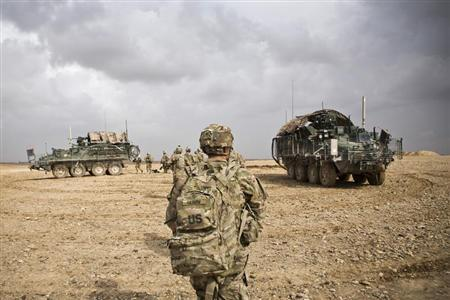 U.S. Army soldiers with Charlie Company, 36th Infantry Regiment, 1st Armored Division head back to their vehicles at the end of a mission near Command Outpost Pa'in Kalay in Maiwand District, Kandahar Province, February 3, 2013. REUTERS/Andrew Burton