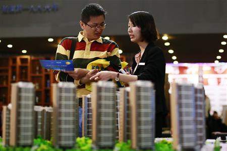 A salesperson (R) talks to a customer behind models of a residential compound at a real estate exhibition in Wuxi, Jiangsu province May 18, 2013. REUTERS/Stringer