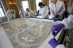 Conservators at the Library of Congress screw down the map that first used the name America as it is prepared for its encasement in Washington December 3, 2007. The 500-year-old map, created by German monk Martin Waldseemuller, is the only known surviving copy and was purchased for $10 million in 2003. REUTERS/Jim Young