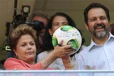 """Presidente Dilma Rousseff mostra a bola autografada por ela ao lado do governador de Brasília, Agnelo Queiroz, durante inauguração do Estádio Nacional Mané Garrincha, em Brasília. Dilma adotou tom otimista ao inaugurar o estádio e criticou neste sábado o """"complexo de vira-lata"""" daqueles que apostavam que o Brasil não entregaria as seis arenas acertadas com a Fifa a tempo da Copa das Confederações no mês que vem. 18/05/2013. REUTERS/Ueslei Marcelino"""