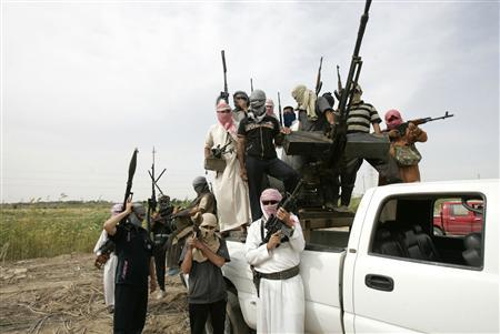 Tribal men pose with their weapons as they patrol a road north of Ramadi, 100 km (62 miles) west of Baghdad, May 18, 2013. REUTERS/Ali al-Mashhadani