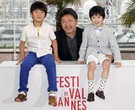 """Diretor Japonês Hirokazu Kore-eda posa com membros do elenco de seu filme 'Soshite Chichi Ni Naru' (""""Tal Pai, tal filho"""") no 66º Festival de Cannes. O longa sobre troca de bebês, que põe em questão a natureza versus criação, estreou no sábado no Festival de Cinema de Cannes e já se tornou um dos favoritos ao prêmio principal, ao lado de uma produção iraniana também elogiada. 18/05/2013. REUTERS/Regis Duvignau"""