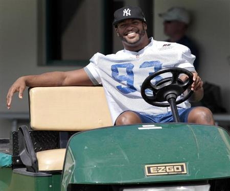 Injured Indianapolis Colts defensive end Dwight Freeney smiles as he drives a golf cart before practice at the Miami Dolphins training facility in Davie, Florida February 6, 2010. REUTERS/Hans Deryk