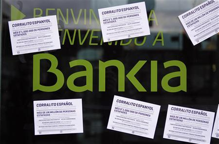 A vandalized Bankia's bank office with papers stuck on it, is seen in Barcelona May 16, 2013. The papers read as ''Spanish 'corrallito' of LaCaixa and 52 other banks. More than a million people cheated, 8.25% of the Spanish population''. REUTERS/Albert Gea