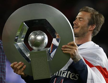 Paris Saint-Germain's David Beckham raises the French Championship trophy at the end of their team's French Ligue 1 soccer match against Brest at the Parc des Princes stadium in Paris May 18, 2013. REUTERS/Gonzalo Fuentes