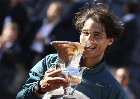 Rafael Nadal of Spain bites the trophy after winning the men's singles final match against Roger Federer of Switzerland at the Rome Masters tennis tournament May 19, 2013. REUTERS/Alessandro Bianchi