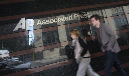 A couple walk past the offices of the Associated Press in Manhattan, New York May 13, 2013. REUTERS/Adrees Latif