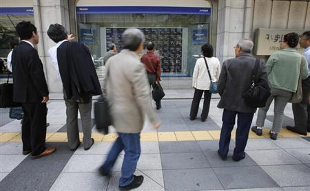 People look at a stock quotation board outside a brokerage in Tokyo May 15, 2013. REUTERS/Toru Hanai