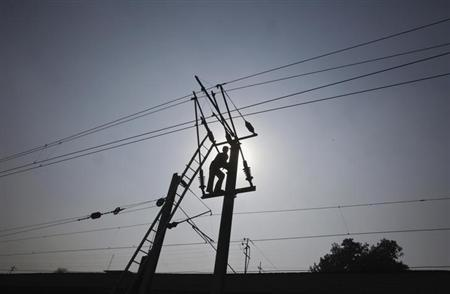 A technician is silhouetted as he works on power lines supplying electricity in the outskirts of Lahore January 31, 2012. REUTERS/Mohsin Raza