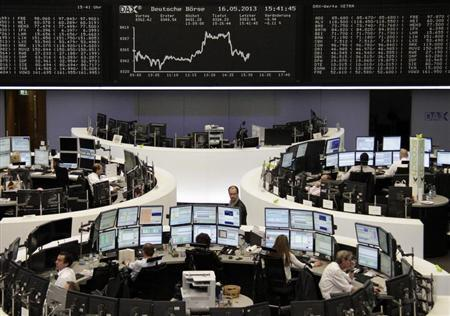 Traders work at their desks in front of the DAX board at the Frankfurt stock exchange May 16, 2013. REUTERS/Remote/Lizza David