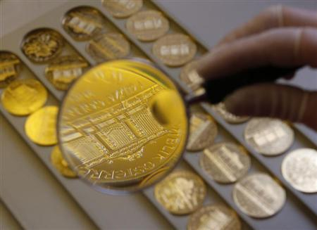 A worker at the Austrian Mint (Muenze Oesterreich) checks a gold Vienna Philharmonic bullion coin for defects in the company's headquarters in Vienna April 23, 2013. REUTERS/Leonhard Foeger/Files