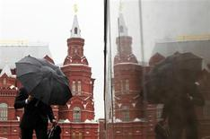 Мужчина с зонтом около Красной площади в Москве 18 мая 2011 года. Рабочая неделя принесет в российскую столицу прохладу и осадки, прогнозируют синоптики. REUTERS/Denis Sinyakov