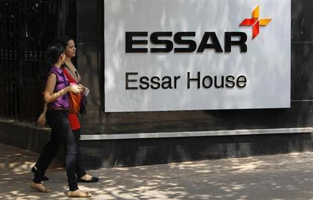 Employees walk past an Essar Group logo outside their headquarters in Mumbai May 20, 2013. REUTERS/Vivek Prakash