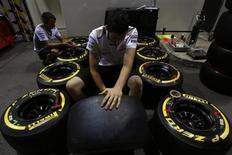 Membro da equipe McLaren inspeciona os pneus da Pirelli antes do início dos treinos para o GP de Cingapura. Os novos pneus a serem introduzidos neste mês na Fórmula 1 causarão mudanças menos dramáticas do que alguns esperavam, ou temiam, disse a fornecedora Pirelli nesta segunda-feira. 20/09/2012. REUTERS/Edgar Su