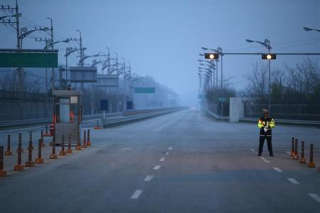 A South Korean police officer stands guard on an empty load connecting the Kaesong Industrial Complex (KIC) inside the North Korean border with the South's CIQ (Customs, Immigration and Quarantine), just south of the demilitarized zone separating the two Koreas, in Paju, north of Seoul May 3, 2013. REUTERS/Kim Hong-Ji