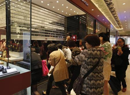 Mainland Chinese visitors enter a jewellery store opening for daily business inside a shopping mall in Hong Kong near the border with mainland China April 23, 2013. REUTERS/Bobby Yip/Files