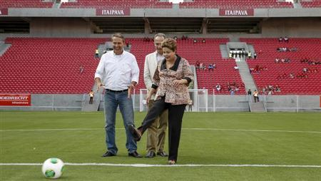 Brazil's President Dilma Rousseff (R) kicks a soccer ball as she inaugurates the Arena Pernambuco stadium along with sports minister Aldo Rebelo (C) and Pernambuco State Governor Eduardo Campos, in Sao Lourenco da Mata, a suburb of Recife, May 20, 2013. Roberto Stuckert Filho-Planalto Palace/Handout via Reuters