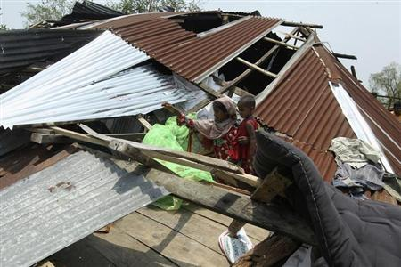 A woman tries to retrieve her belongings after her house has been destroyed by cyclone Mahasen, in Kuakata May 17, 2013. REUTERS/Stringe