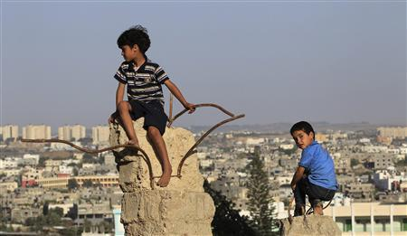 Palestinian boys sit atop remains of a house in Beit Lahiya, in the northern Gaza Strip May 20, 2013. REUTERS/Mohammed Salem
