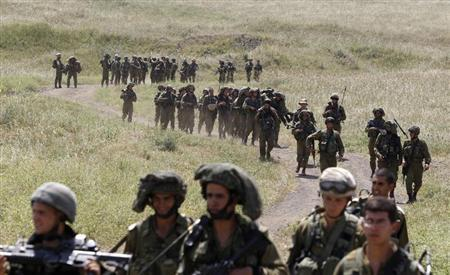 Israeli soldiers walk together during a training close to the ceasefire line between Israel and Syria on the Israeli occupied Golan Heights May 7, 2013. REUTERS/Baz Ratner