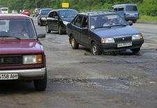 Cars drive over a pothole along a road near Kiev May 16, 2013. REUTERS/Gleb Garanich