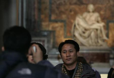 Tourists pose in front of the world famous Michelangelo's Pieta' in Saint Peter's Basilica at the Vatican January 18, 2005. REUTERS/Tony Gentile/Files